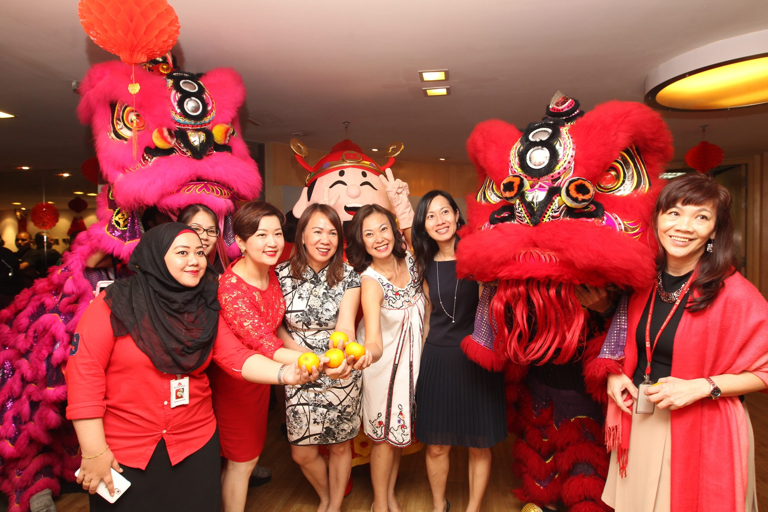 Mah Sing staff members posing for a photo with the lions during the Star Media Group visit to usher in the Year of the Rooster together.