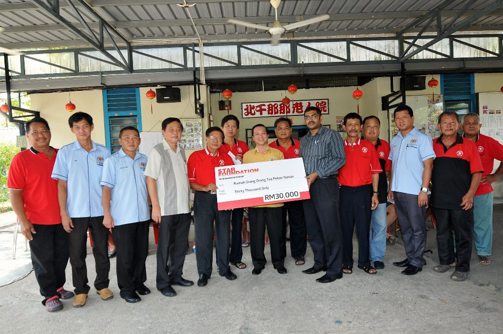 Useful boost: The Star Johor Bureau chief Nelson Benjamin presenting a RM30,000 mock cheque from Star Foundation to Ong (fifth from left). Looking on is Datuk Wee (in yellow).