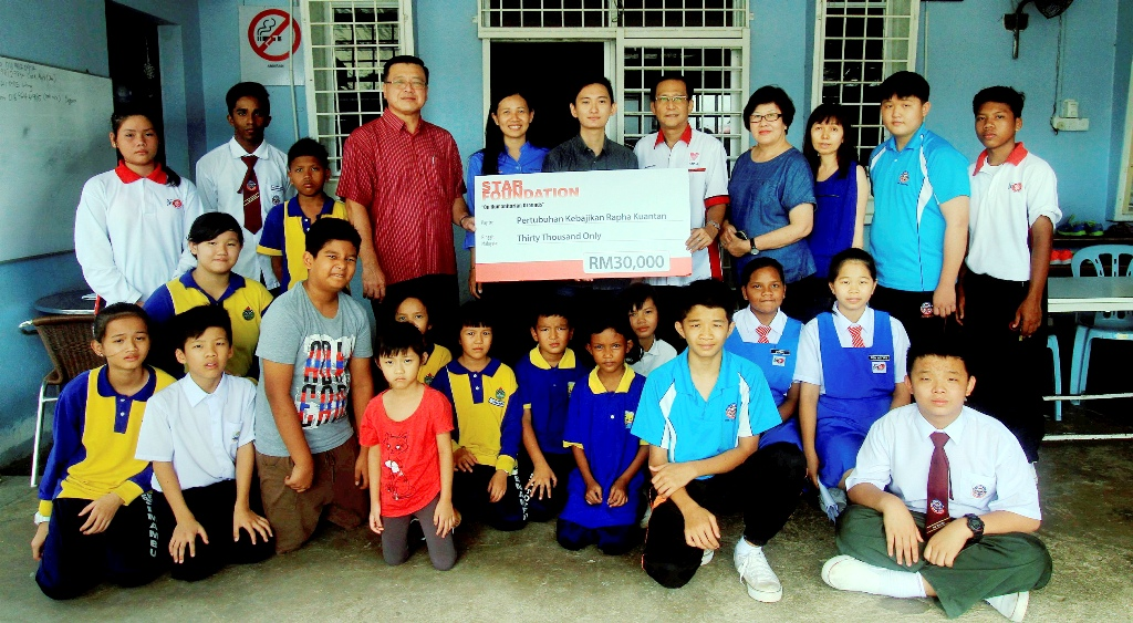 Generous donation: Committee members and several children of Rapha Children's Home posing for a picture after receiving a mock cheque from The Star journalist Ong Han Sean (centre). Looking on are Wong (fourth from left, standing) and Tee (to Ong's right).