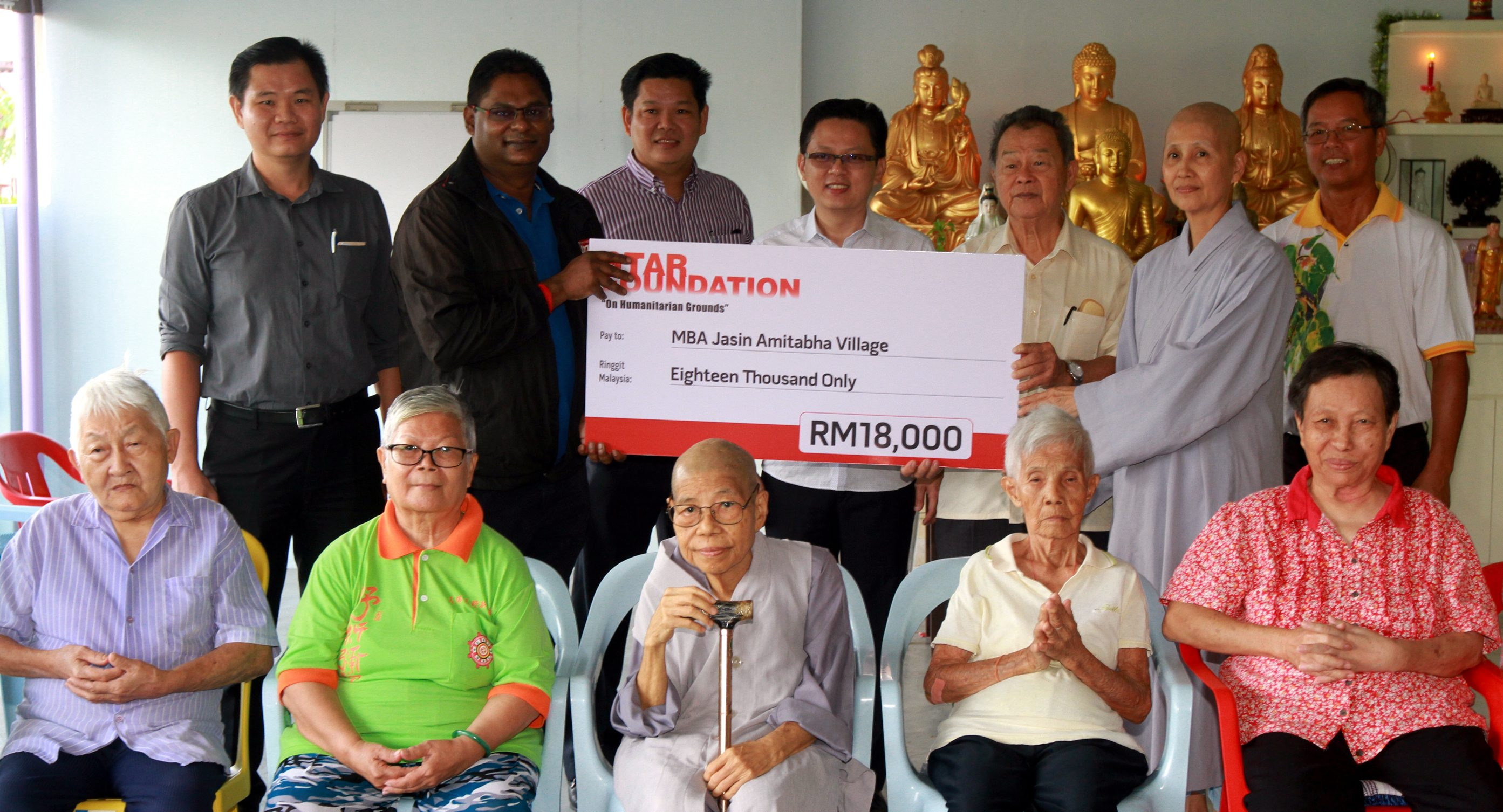 Generous gesture: Malacca Star Media Group bureau chief R.S.N. Murali handing over the mock cheque to Goh and Lim (third from right). Also present during the presentation is Koh (back row, centre).