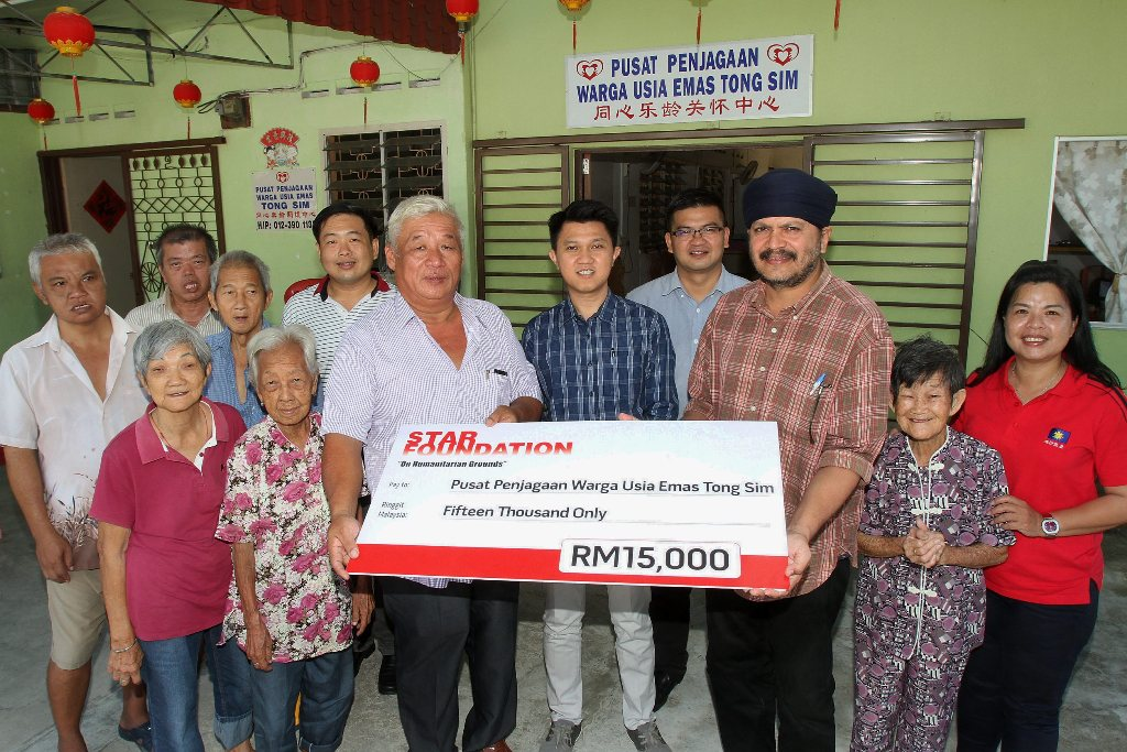 Chinese New Year cheer: The Star journalist Sarban Singh handing over the mock cheque from the Star Foundation to David Chong at the home in Seremban. Looking on are Chong Sin Woon (centre) and MCA Youth legal bureau head Ng Kian Nam (behind David).