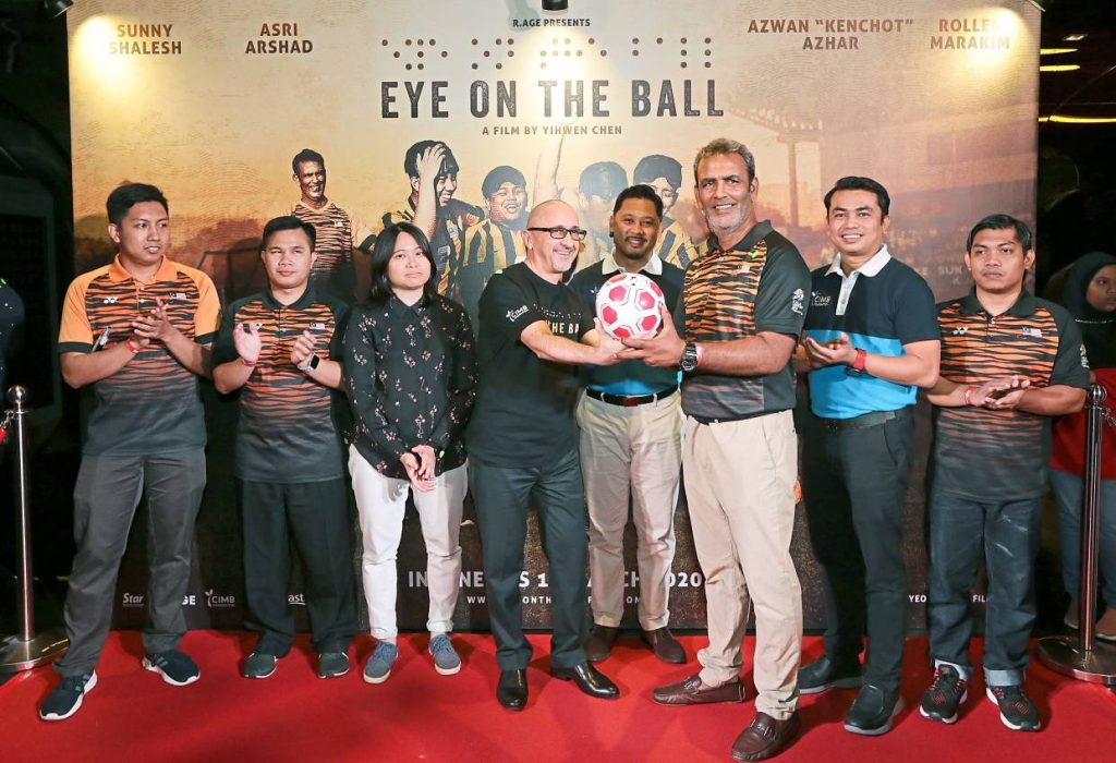 Vogiatzakis (fourth from left) presenting a special ball to Sunny during the 'Eye On The Ball' gala premiere. Also present are (from left) national blind football players Mohd Asri Arshad and Rollen Marakim, Chen, CIMB Foundation acting head of Corporate Responsibility Noorali Abd Razak, CIMB Foundation CSR assistant manager Abdul Rashid Abdul Rahman and player Mohd Azwan.